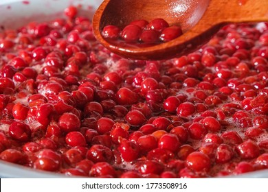 Bowl with pitted cherries. Fragrant cherry in its juice for jam. In a wooden spoon there are cherries and cherry juice. Homemade food concept. Hobby concept. Copy space.