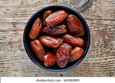 Bowl of pitted dates on wooden background, top view