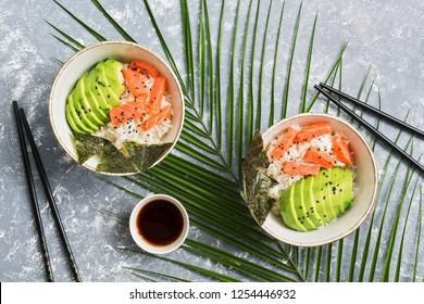 Bowl poke with salmon, rice, avocado and nori on a gray background with soy sauce and tropical leaves. Top view, flat lay