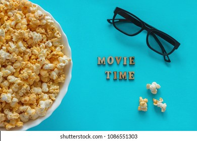 "bowl of popcorn, 3D glasses, Text ""Movie Time"". Still life on blue background. Flat lay, Top view. Concept pastime, entertainment and cinema."