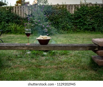 Bowl of popcorn and glass of wine stand on a bench with a campfire behind
