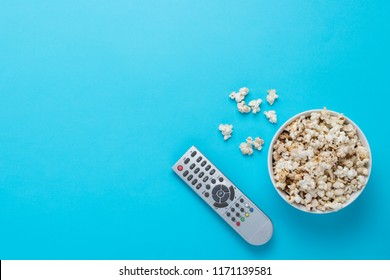 Bowl with popcorn and remote control for TV on a blue background