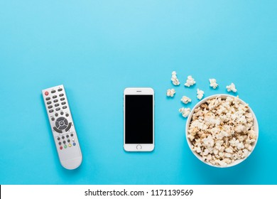 Bowl with popcorn, remote from the TV, white phone on a blue bac