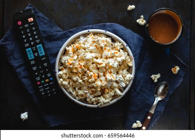 Bowl of popcorn with salted caramel, remote control TV, glass with milk on a blue tablecloth. View from above. Leisure. Watch TV.