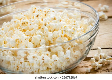 Bowl Of Popcorn - This is a shot of a glass bowl full of hot air popped popcorn on a wooden table. Shot with a shallow depth of field.