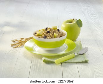 bowl of porridge with apples and prunes on white wood table