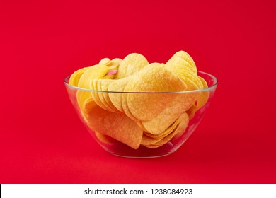 Bowl of potato chips in bright red background. Minimalistic image of attention grabbing fast food in vivid colors