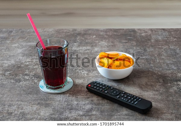 Bowl of potato chips, glass of juice on a drink coaster with a straw in it and a remote control. Chips, glass of coke and remote control isolated on wooden table. Relax and rest at home