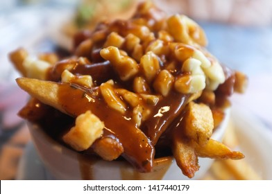 A bowl of poutine in a small French Canadian bistro