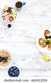 Bowl of puffed rice cereal with pear, oatmeal with blueberry, pancakes and cup of coffee on white table. Summer breakfast food frame with empty space.