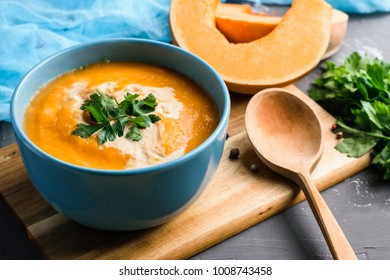 Bowl of pumpkin and carrot soup with cream. Vegan healthy food.