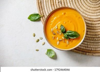 Kürbis- oder Karottensuppe, mit frischen Basilikum, Olivenöl und Kürbiskerne auf weißem Hintergrund mit Zutaten oben. Flachlage, Kopienraum
