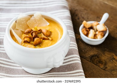 Bowl of pumpkin cream soup with fried chanterelles, sliced parmesan and croutons on the napkin and wooden background.