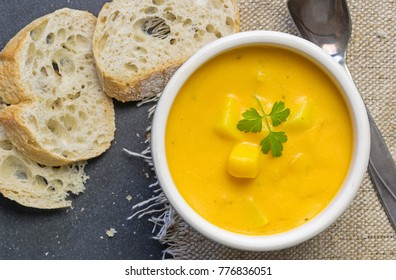 A bowl of pumpkin potato vegetable soup with bread and garnish
