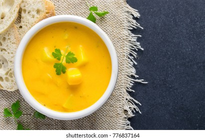 A bowl of pumpkin potato vegetable soup with bread and garnish on a dark background with copy space for your text