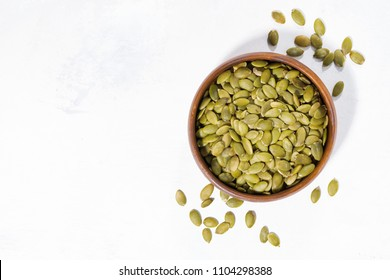 bowl with pumpkin seeds on white background, top view horizontal