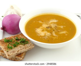 A bowl of pumpkin soup and garlic toast