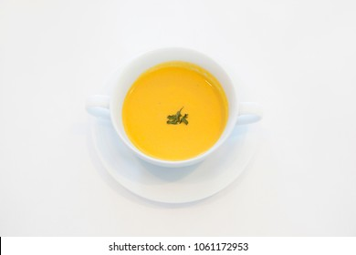Bowl of pumpkin soup isolated on a white background