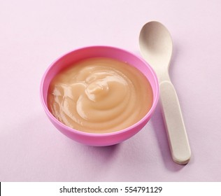bowl of pureed apple on purple background
