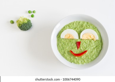 Bowl of pureed green vegetables for baby with happy face made by egg and vegetables