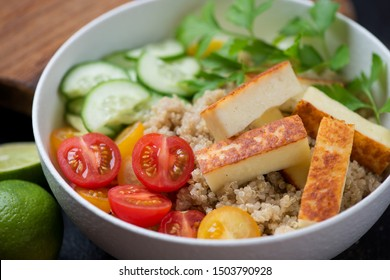 Bowl with quinoa, fried cheese, cherry tomatoes, cucumber and parsley, close-up, selective focus