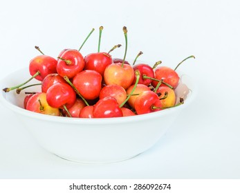 A bowl of Rainier cherry on isolated white background. Rainiers are sweet cherries with a thin skin and thick creamy-yellow flesh. Copy space.