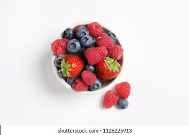 Bowl with raspberries, strawberries and blueberries on white background