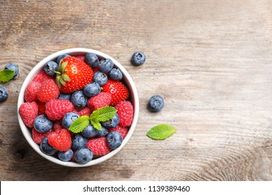 Bowl with raspberries, strawberries and blueberries on wooden table, top view