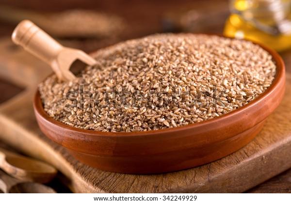 A bowl of raw bulgar wheat against a rustic background.