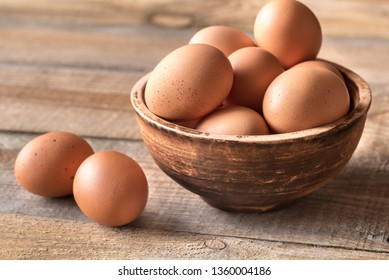 Bowl of raw chicken eggs on the wooden background