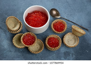Bowl with red caviar and tartlets over blue stone background, horizontal shot