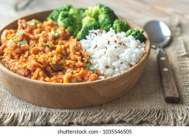 Bowl of red lentil curry with white rice and broccoli