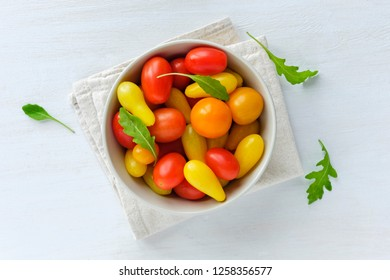 Bowl of red and yellow tomatoes decorated with edible chicory green leaves, viewed from above on white wooden background. Concept of homegrown harvest of organic food