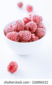 Bowl of refreshing frozen raspberries covered in frosting for a delicious healthy dessert, tilted closeup angle