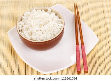 Bowl of rice and chopsticks on plate on bamboo mat