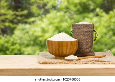 A bowl of rice on wooden table, outdoor plant background