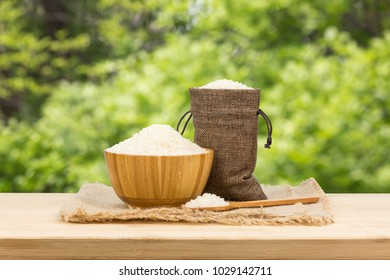 A bowl of rice on wooden table, green plant background