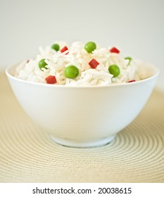 bowl of rice with peas and red peppers