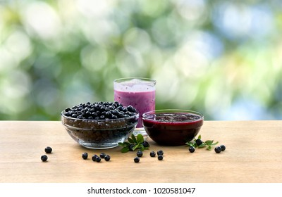 Bowl with ripe berries wild bilberries, bowl with jams of bilberries and of fruit yogurt on wooden table on defocused of natural background with space for text
