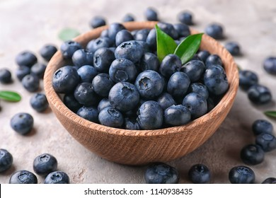 Bowl with ripe blueberries on light table