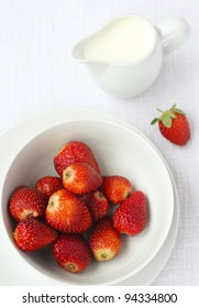 A bowl of ripe strawberries with a jug of cream in the background