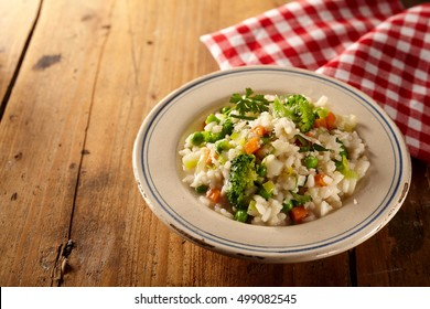 Bowl of risotto risi bisi and veggies beside checkered napkin over wooden table with copy space and pleasing light