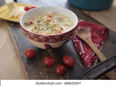 A bowl of roasted cauliflower chowder with a side of cherry tomatoes and sliced cheddar cheese.
