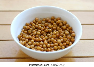 Bowl of roasted crispy chickpeas on wooden table. Selective focus.