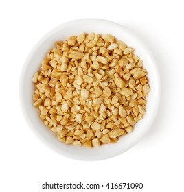 Bowl of roasted crushed peanuts isolated on white background, top view