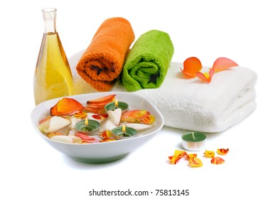 bowl with  rose petals, rose candle  and towels on white background