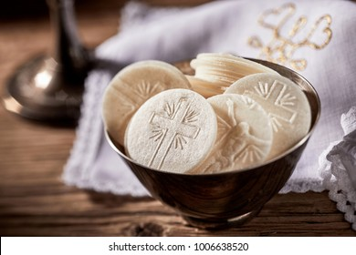 Bowl of sacramental bread or Hosties ready for the Holy Communion service representing the body of the resurrected Christ showing detail of the cross