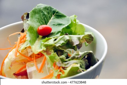 Bowl of salad with cherry tomato on top