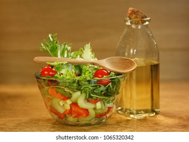 Bowl of salad with fresh vegetables and olive oil on wooden background