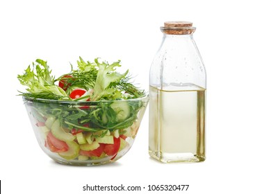 Bowl of salad with fresh vegetables and olive oil, isolated on white background